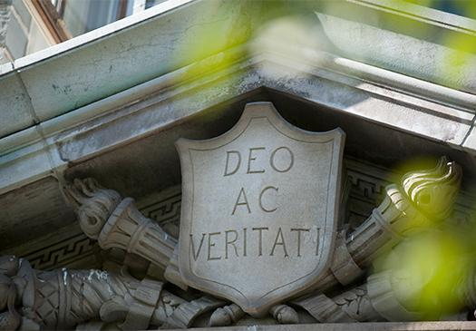 "An image of a stone carving with the motto, ""Deo Ac Veritati"""