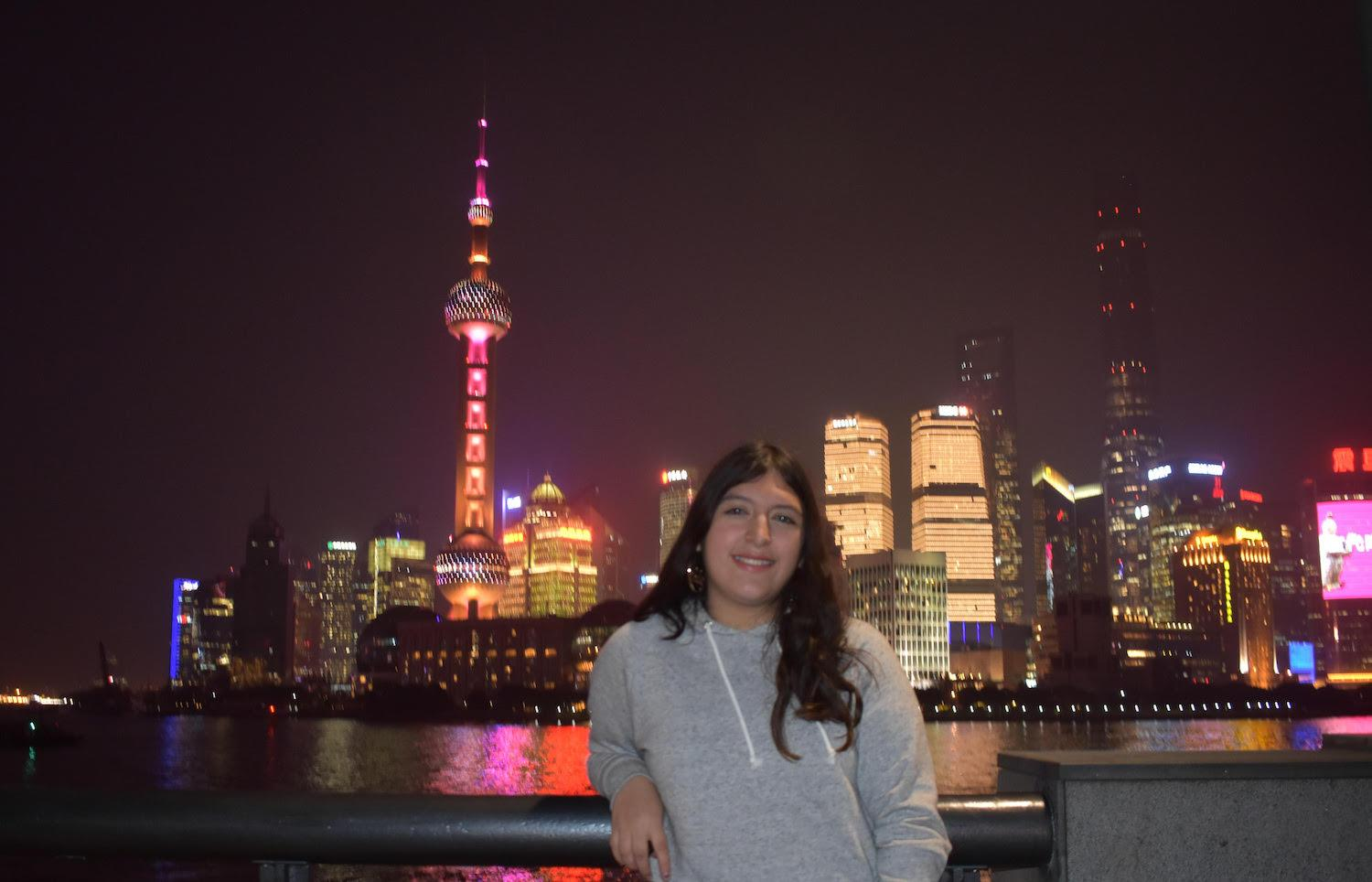 Elizabeth Gonzales with the nighttime Shanghai skyline in the background
