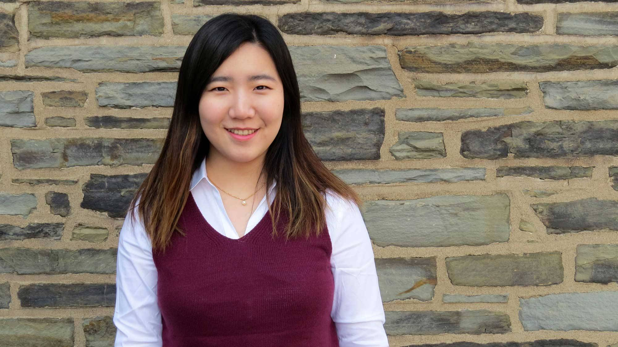 Watson Fellowship winner Minjoo Kim '20 in front of a stone wall