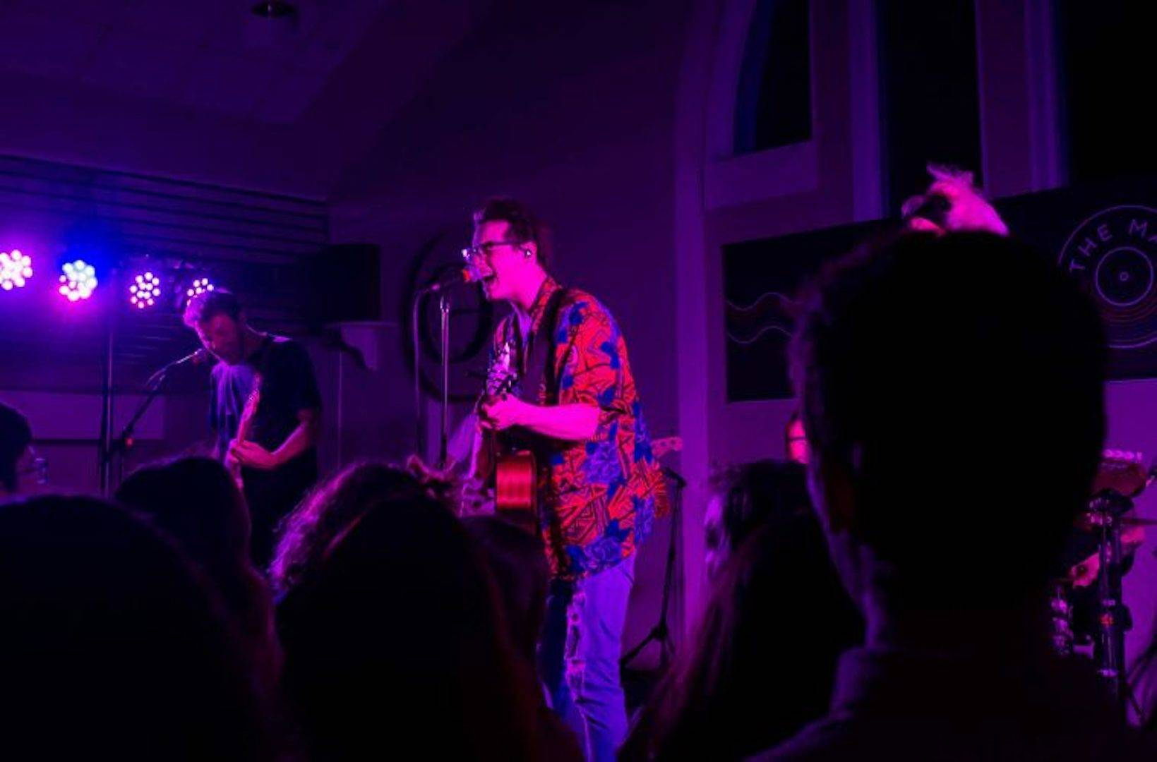 Male singer sings into mic during an intimate, darkly lit pop-rock performance