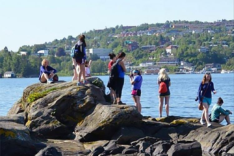 Students climb on a rocky outcrop near the water