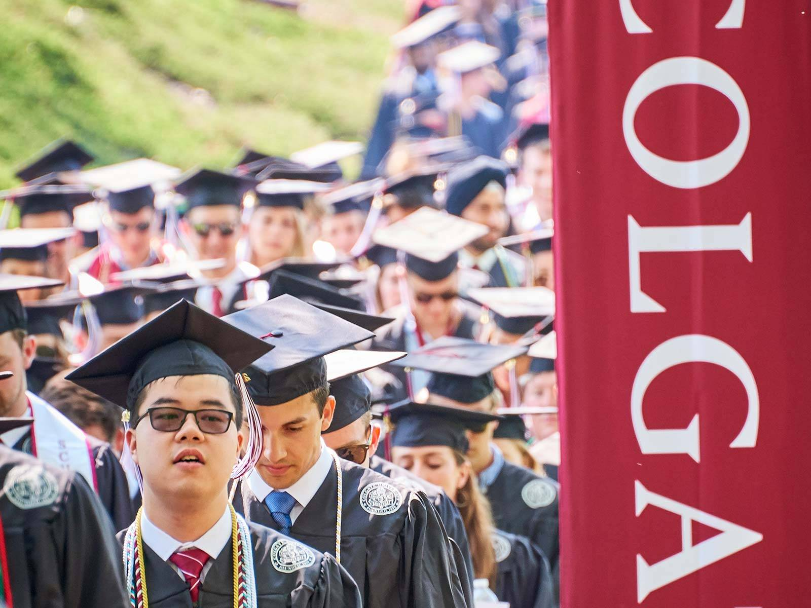Students process into commencement 2019 past a Colgate Banner