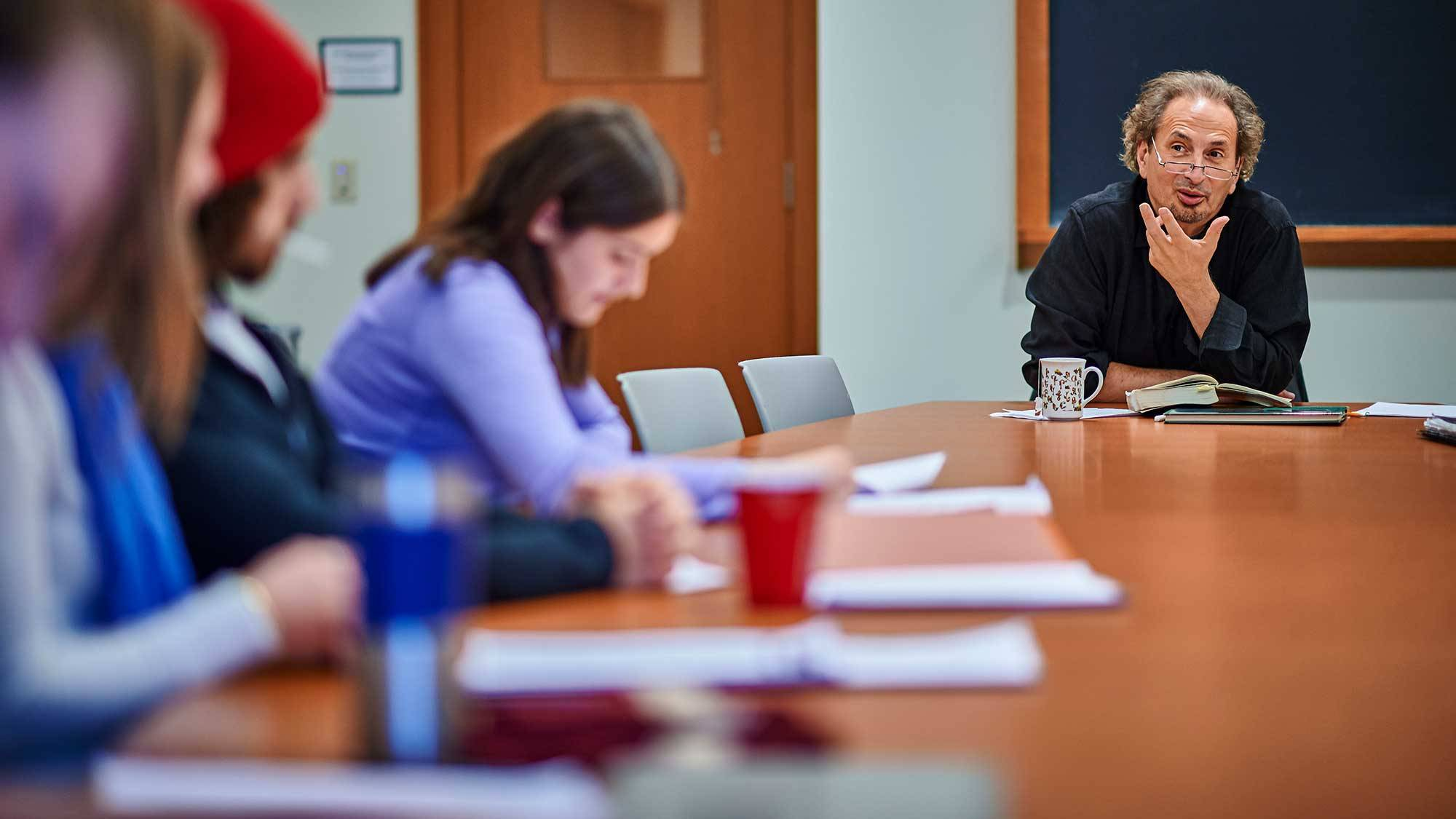 Peter Balakian teaches students around a table