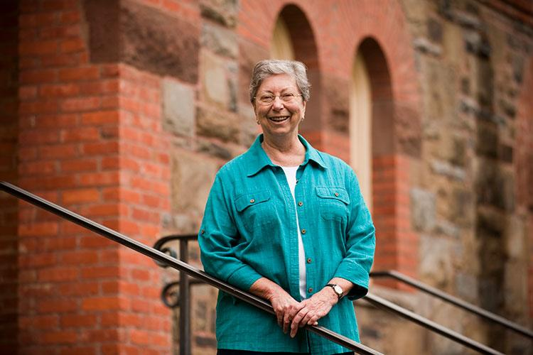 Portrait of Marilyn Thie, professor of philosophy, religion, and women's studies, on the steps of Hascall Hall